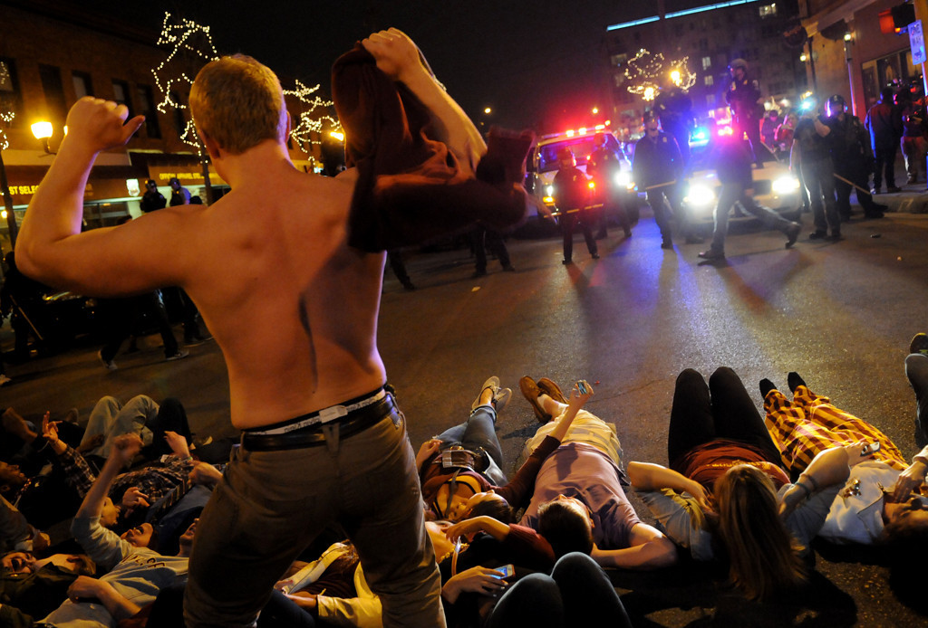 . Minnesota hockey fans lie in the intersection as one fan dances without a shirt as Minneapolis police line up in riot gear along 4th and 14th in Dinkytown on Saturday night after the loss to Union College. (Pioneer Press: Sherri LaRose-Chiglo)