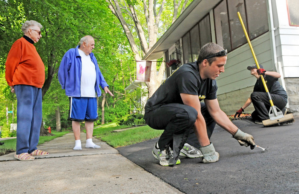 . Opal and Bob Kuehn, left, talk to a crew from Jet-Black, Trevor Funk and Kayla Khamthanie, right, as they reseal the Kuehns\' driveway in St. Paul. (Pioneer Press: Jean Pieri)
