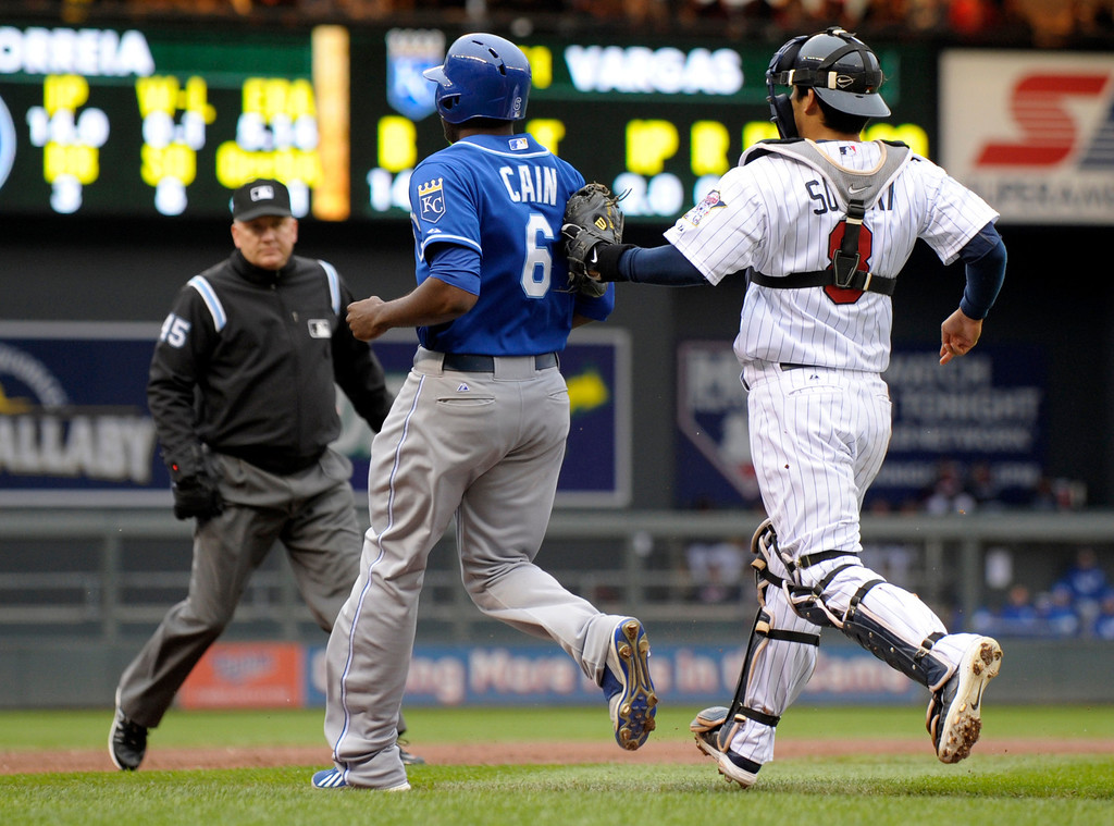 . Minnesota Twins catcher Kurt Suzuki, right, tags out Kansas City Royalsí Lorenzo Cain (6) after getting caught in a rundown between third base on home plate during the third inning. Umpire Jeff Nelson looks in to make the call. (AP Photo/Tom Olmscheid)