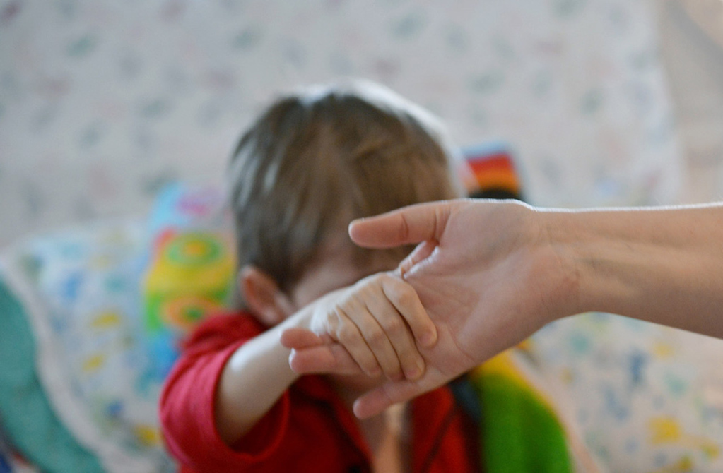 . Cameron Ulrich pulls on his mom Kari\'s hand to get a boost up in bed in his room.   (Pioneer Press: Richard Marshall)