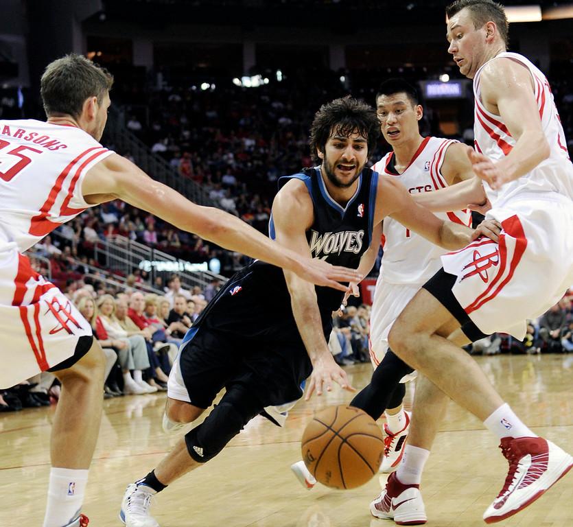 . Minnesota Timberwolves\' Ricky Rubio, center, drives the ball between Houston Rockets Chandler Parsons (25), Jeremy Lin (7) and Donatas Motiejunas, right. (AP Photo/Pat Sullivan)