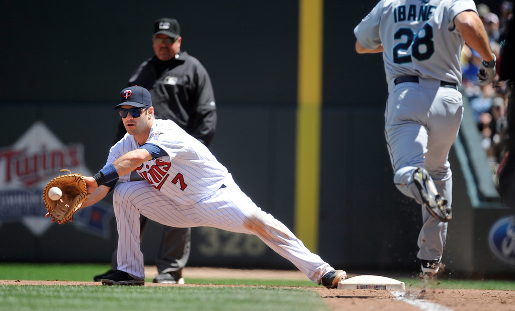 . Minnesota Twins first baseman Joe Mauer, left, gets Seattle Mariners\' Raul Ibanez out at first during the fourth inning of a baseball game on Sunday, June 2, 2013, in Minneapolis. (AP Photo/Craig Lassig)