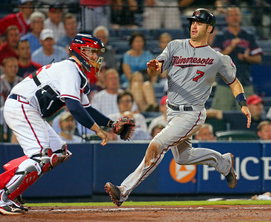 . The Minnesota Twins\' Joe Mauer scores as Atlanta Braves catcher Brian McCann awaits the throw on an RBI single by Trevor Plouffe in the eighth inning at Turner Field in Atlanta on Tuesday, May 21, 2013. (Curtis Compton/Atlanta Journal-Constitution/MCT)