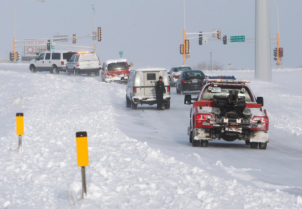 . A Rochester Police officer directs traffic around a pair of vehicles stuck on the off-ramp to West Circle Drive from Highway 14 in Rochester Friday morning.  (Rochester Post-Bulletin: Ken Klotzbach)