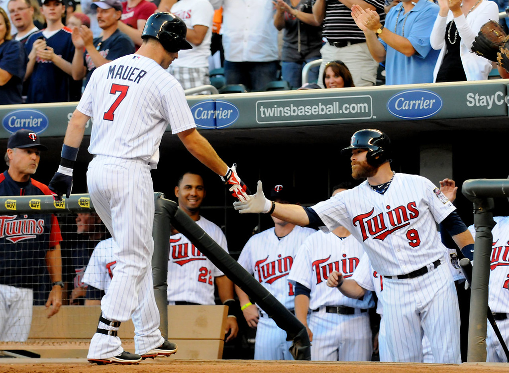 . Joe Mauer is welcomed back to the dugout by Ryan Doumit after hitting a solo home run. (Pioneer Press: John Autey)